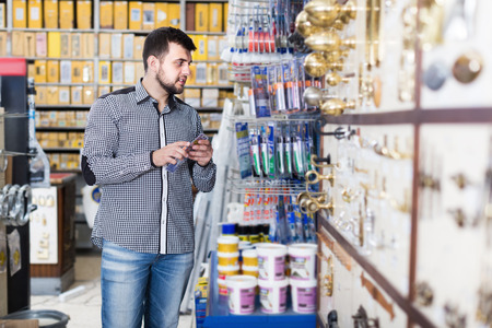 Smiling man client choosing new glue in houseware store Imagens