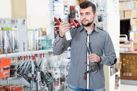 Smiling man customer choosing new glue in houseware shop