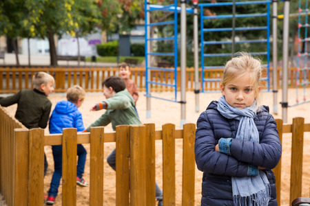 Portrait of offended girl not playing with friends after quarrel on playground