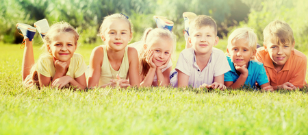 portrait of smiling european children lying on grass in park and looking happy