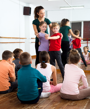 Beautiful children studying modern style dance in class and their young teacher