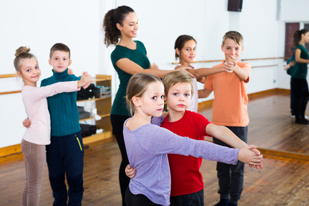 positive children dancing tango in dance studio