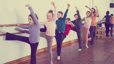 friendly children primary school age rehearsing ballet dance in studio