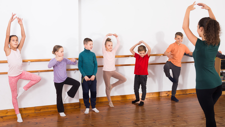 industrious boys and girls primary school age rehearsing ballet dance in studio 版權商用圖片