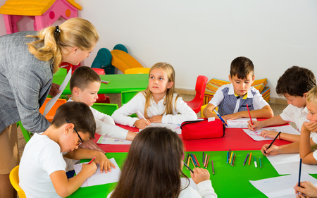 Glad cheerful positive  female teacher helping schoolkids drawing with color pencils in classroom