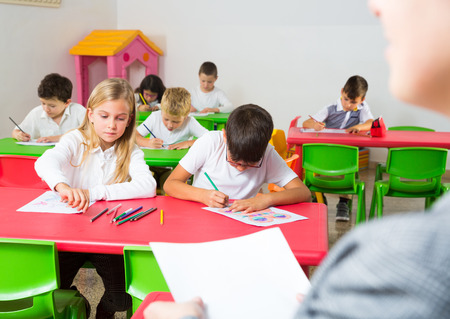 Group of school kids with pens and notebooks studying in classroom with teacher