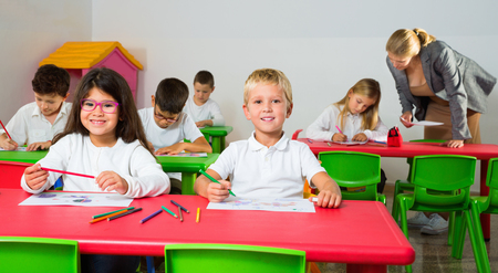 Happy  positive smiling female teacher helping schoolkids drawing with color pencils in classroom