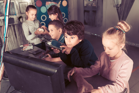 Group of smiling children are concentrating on finding a way out of bunker quest room