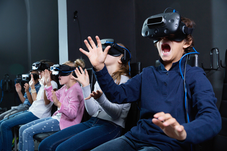 Enthusiastic  cheerful positive  children in virtual reality glasses in quest room Stock Photo