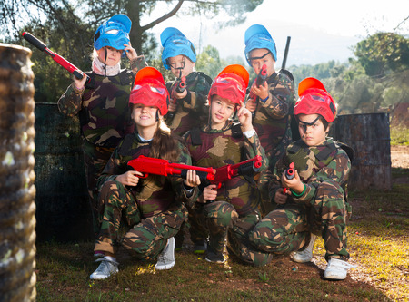 Portrait of group of boys and girls paintball players with marker pistols ready for game outdoors