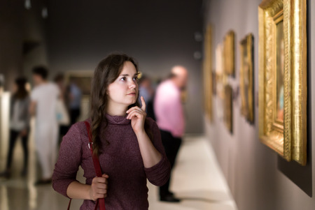 Portrait of cheerful young girl attentively looking at paintings in art museum Imagens