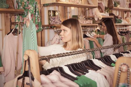 Woman customer looking green striped long sleeve shirt  in  fashion store