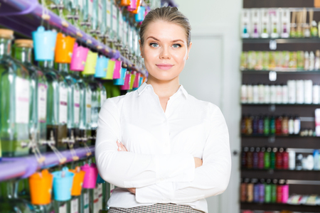 Successful young saleswoman standing in perfume store