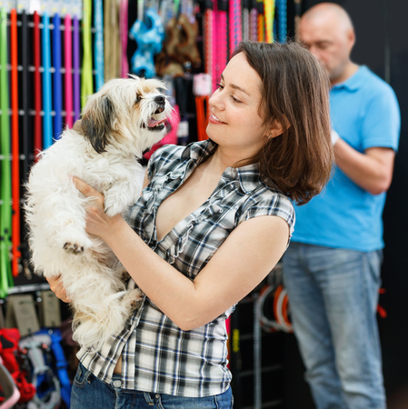 Happy pleasant smiling young woman with dog in pet store during shopping with man