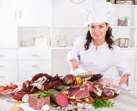 Young brunette girl shows a sausages and smoked products which lie on a table