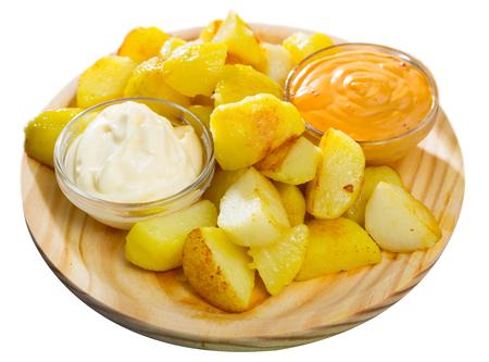 Patatas bravas with garlic mayonnaise and sauce. Isolated over white background 版權商用圖片
