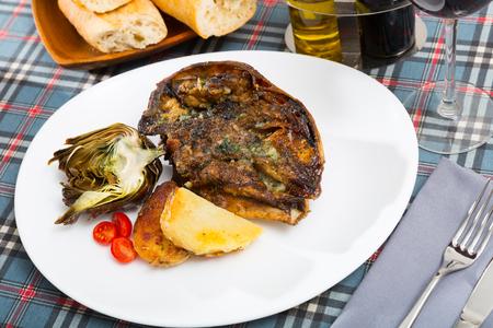 Cabeza de cordero - spanish dish. Lamb head with artichoke, tomatoes and potatoes Foto de archivo - 116718453