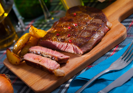 Appetizing deep-fried beef  with potato served on cutting board