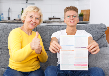 Happy senior mother and her adult son reading brochure with event announcements on sofa at kitchen Imagens
