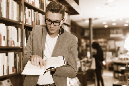 Serious positive man pointing at something in open book at bookstore