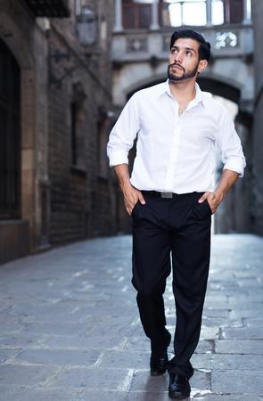 Handsome bearded man walking along old town street