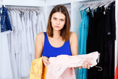 Upset angry young woman trying to choose dress in clothing showroom