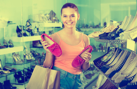 joyful teenager girl choosing pair of shoes in fashion  boutique and smiling