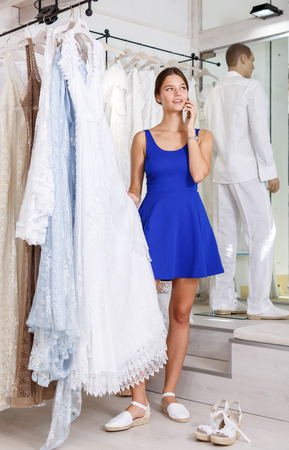 Young attractive girl choosing wedding dress and talking on her mobile phone at wedding salon