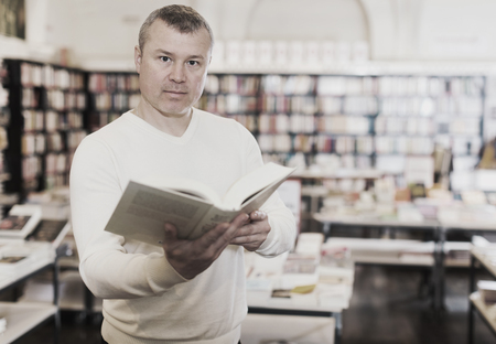 Intelligent man reading interesting books in bookstore Foto de archivo