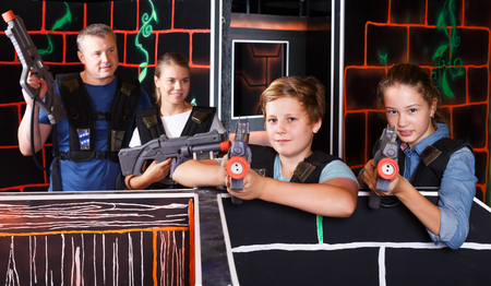 Smiling teenage boy and girl with laser guns having fun with adults in dark lasertag labyrinth