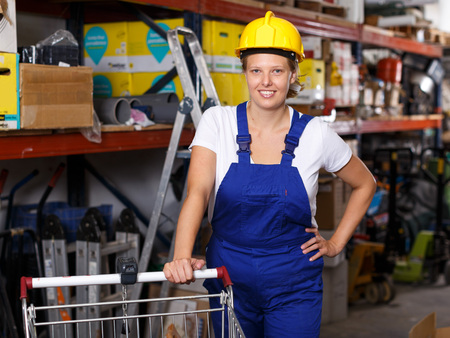Young woman  in uniform and helmet standing near basket with tools  in build store Imagens - 116876657