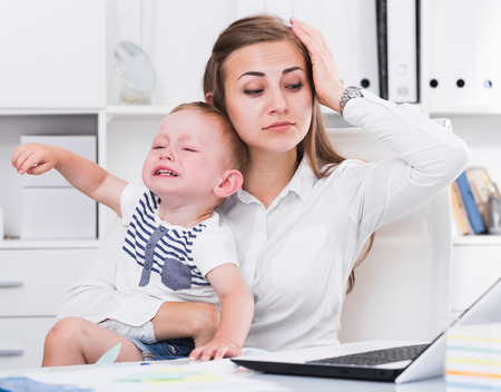 Woman is working with a naughty child in her arms behind a laptop in the office.