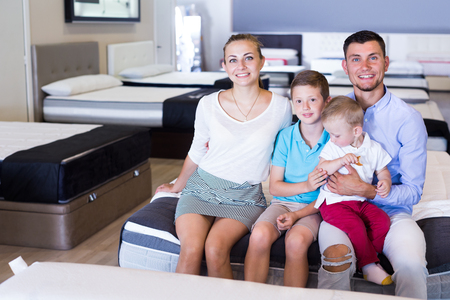 Happy family sitting on bed in store, testing quality of mattress