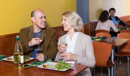 Mature man and woman drinking wine together in restaurant Banco de Imagens