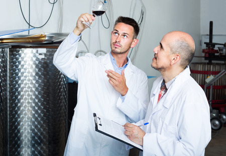 two positive european men coworkers in white coats working in fermentation section