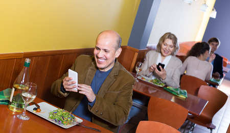 Cheerful smiling mature man with smartphone at the table in restaurant Stockfoto