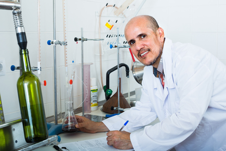 mature professional man working with quality tests in wine manufactory laboratory Imagens