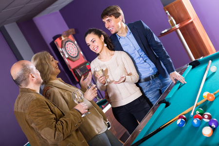 Smiling different age friends with glasses of wine chatting near billiard table Stockfoto