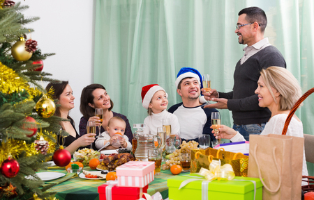 Cheerful Mature parents with kids and grandchildren celebrating Merry Christmas