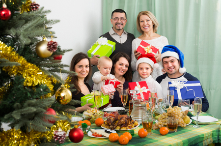 Portrait of big family with presents at the table gathering together for Christmas