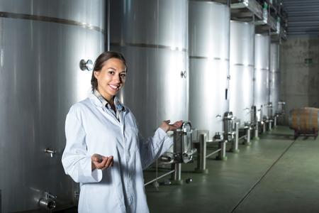 joyful winery female employee wearing coats standing in fermentation section on winery manufactory Stock fotó - 116916428