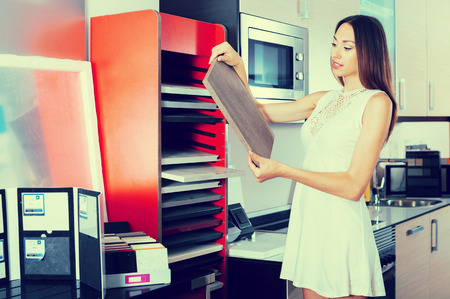 Adult girl choosing kitchen fronts materials for her apartment