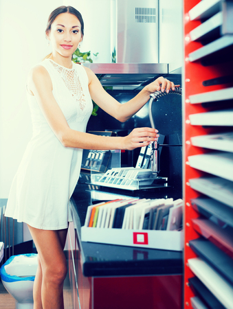 Svelte woman choosing new stylish mixer tap in kitchen furnishing store