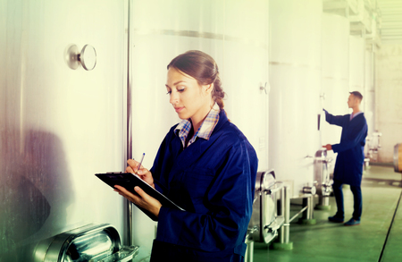 Young woman winery employee in uniform taking off data from equipment in winery fermentation section Stock fotó - 116918995