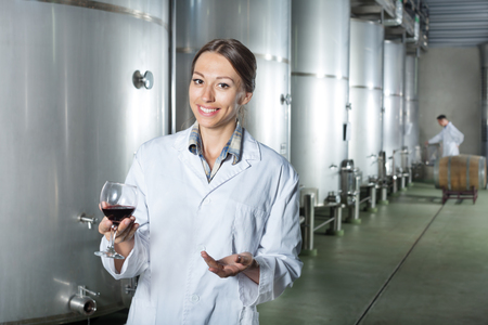Smiling young woman wearing uniform standing with glass of wine in fermenting section on a wine factory Stock fotó - 116918998