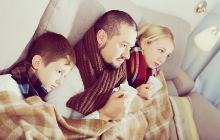 Sick parents and their son with scarf on neck lying on sofa under blanket Banco de Imagens