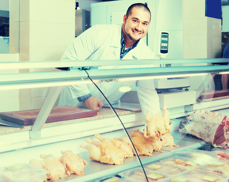 positive spanish  male shop assistant selling kosher chicken at counter and smiling Stock fotó