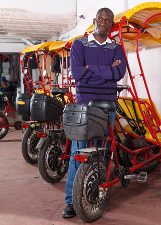 Joyful successful African American driver of pedicab offering touristic tour