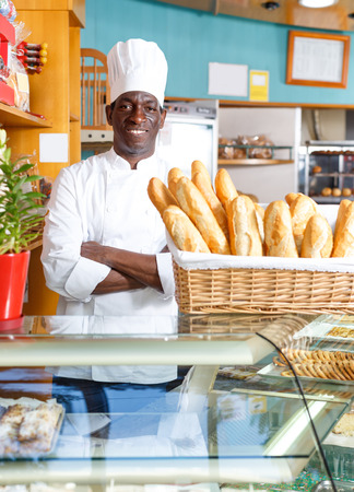 Proud owner of bakery shop wearing white uniform standing with arms folded behind counter with fresh baked products