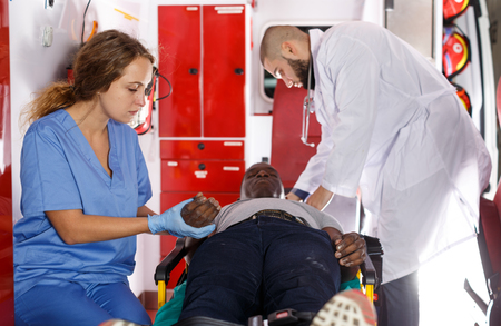 Équipe paramédicale prodiguant les premiers soins à l'homme dans l'automobile d'ambulance